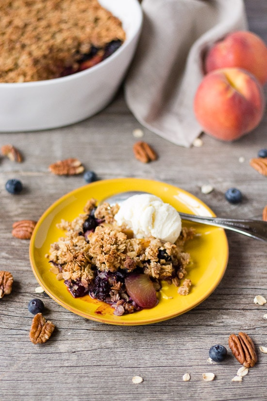 gluten free blueberry peach crisp on a yellow plate with a scoop of ice cream. white dish with crisp, a tan napkin, and two peaches are in the background. Pecans, blueberries and oats are spread around.