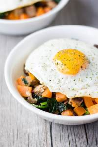 cut up sweet potatoes, pork, and spinach in a white bowl with an over-easy egg on top, on a gray background with another bowl of the same in the upper left