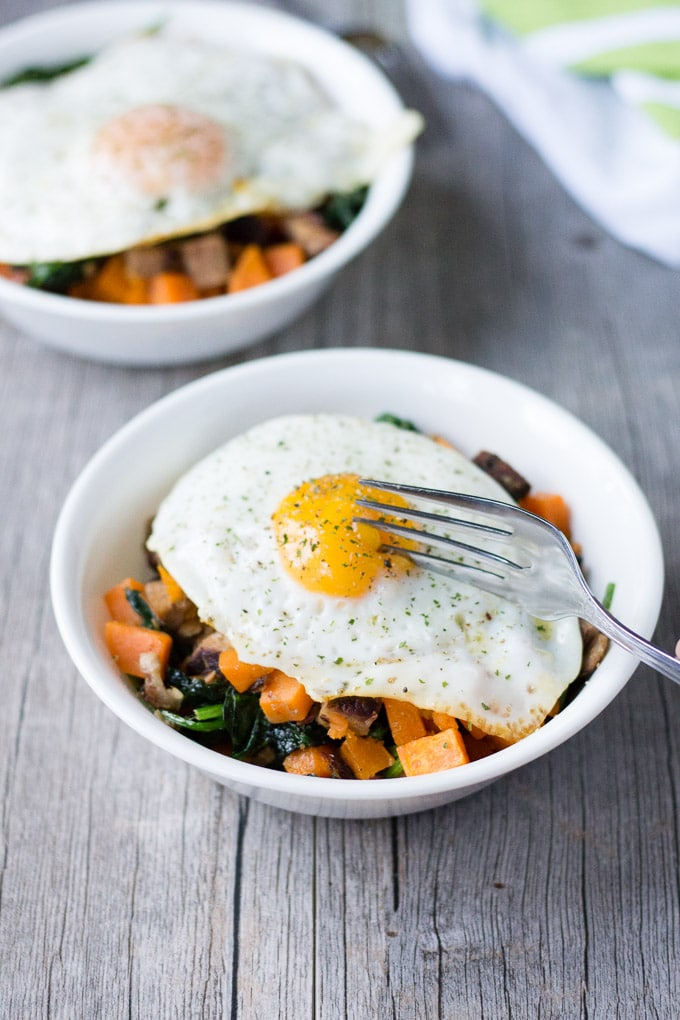 breakfast hash with an over-medium egg on top in a white bowl. A silver fork is barely cutting into the yolk.