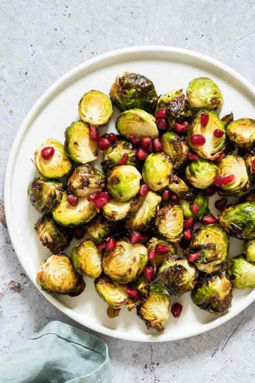 roasted brussels sprouts and pomegranate seeds on a white plate with a light blue napkin in the bottom left corner