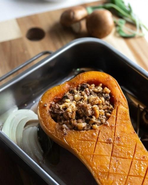 stuffed butternut squash half in a roasting pan on a cutting board