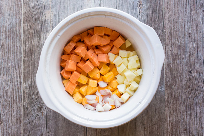 top down view of slow cooker insert with cubed butternut squash, sweet potato, apple, and shallot in it, on a gray background