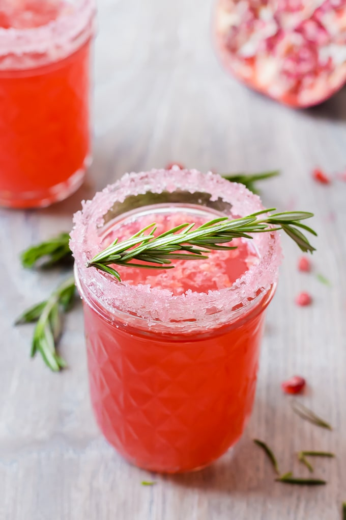small mason jar with pomegranate cocktail and a sugared rim. A spring of rosemary lies across the top and there's another cocktail in the left background.