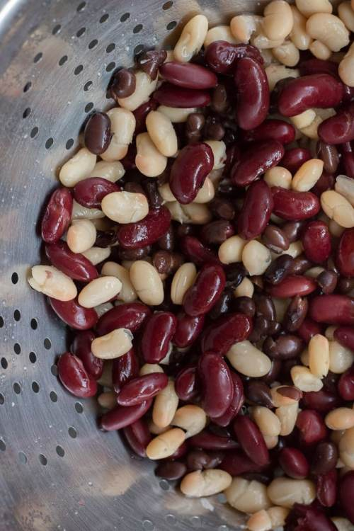 top down shot of beans in a silver colander