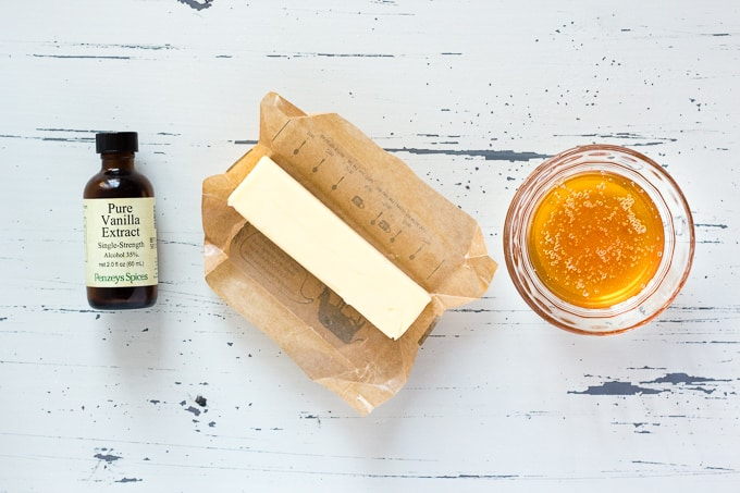 top down view of a stick of butter, a dish with honey in it, and a bottle of vanilla extract