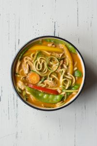 top down view of chicken curry zoodle bowl on an off-white background