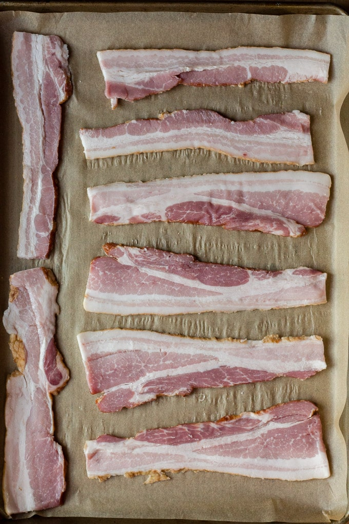 top down view of 8 raw bacon slices on top of parchment paper in a sheet pan