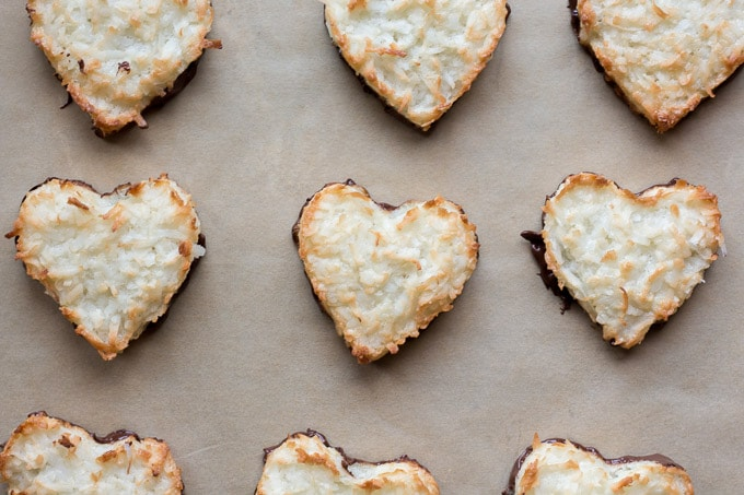 top down view of chocolate dipped chewy coconut macaroon hearts on parchment paper