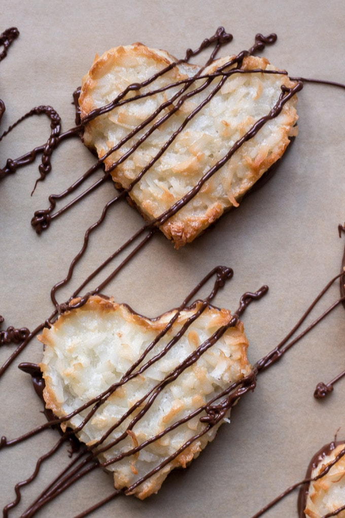 top down view of chocolate drizzled on top of chewy coconut macaroon hearts on parchment paper