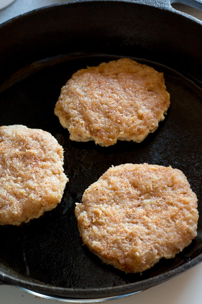 cooking three healthy ground chicken burgers in a cast iron skillet
