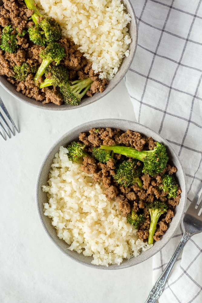 top down shot of two gray bowl with paleo ground beef and broccoli and cauliflower rice