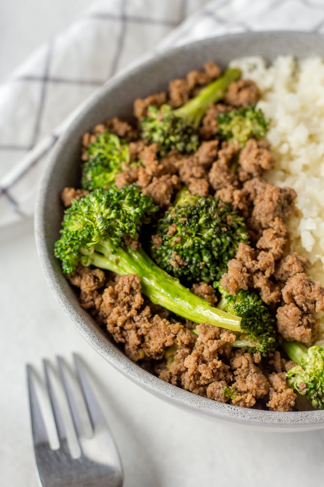 zoomed in shot of paleo ground beef and broccoli in a gray bowl with cauliflower rice