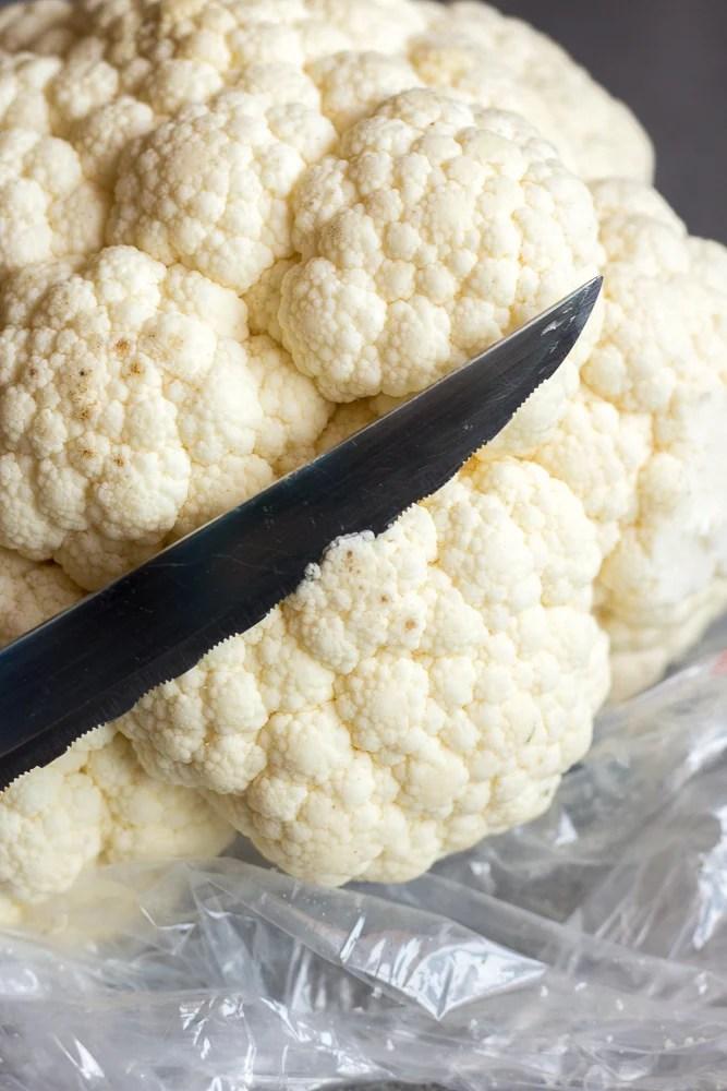 a knife cutting into cauliflower