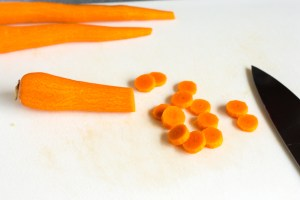 slicing carrots on a cutting board for corn chowder