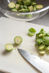 cutting brussels sprouts on a cutting board with a knife