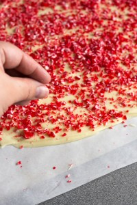 a hand sprinkling peppermint bits onto peppermint bark