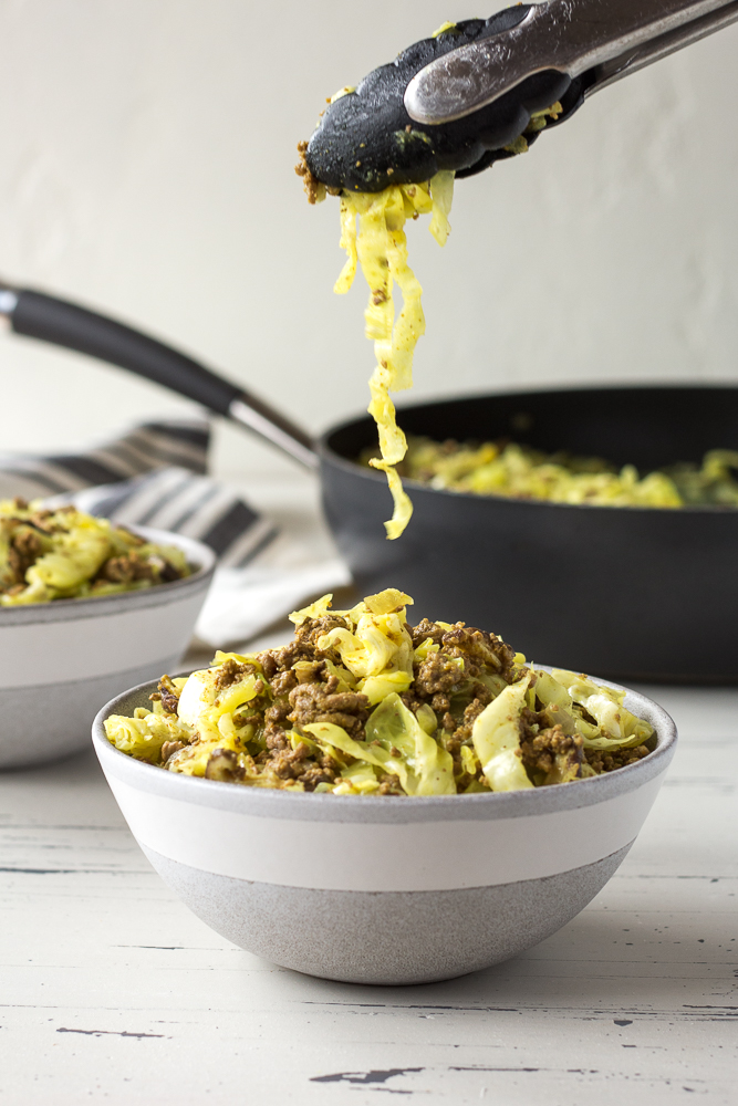 a pair of tongs dropping ground beef and cabbage stir fry into a gray bowl