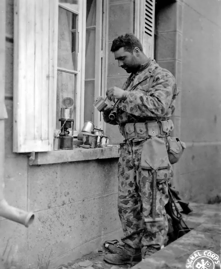 "A U.S. Army soldier in Normandy wearing the one-piece ""frog"" or ""frogskin"" camouflage suit."
