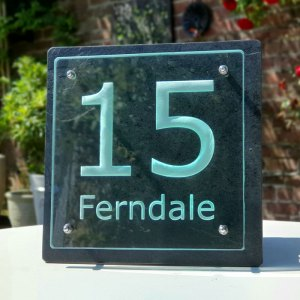 engraved glass, slate and stainless steel outdoor sign in a garden setting with brick wall
