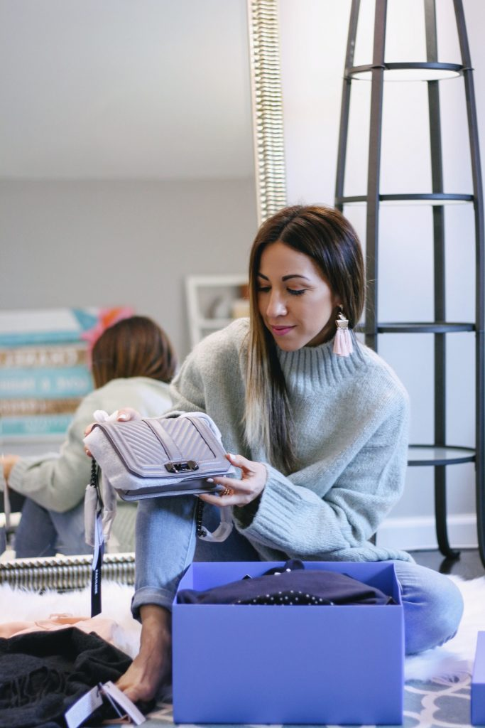 DAILYLOOK BOX REVIEW: SPRING FASHION featured by top New Jersey fashion blog, House of Leo: image of a woman sitting in front of a mirror holding her new Rebecca Minkoff bag, including in her new Dailylook box
