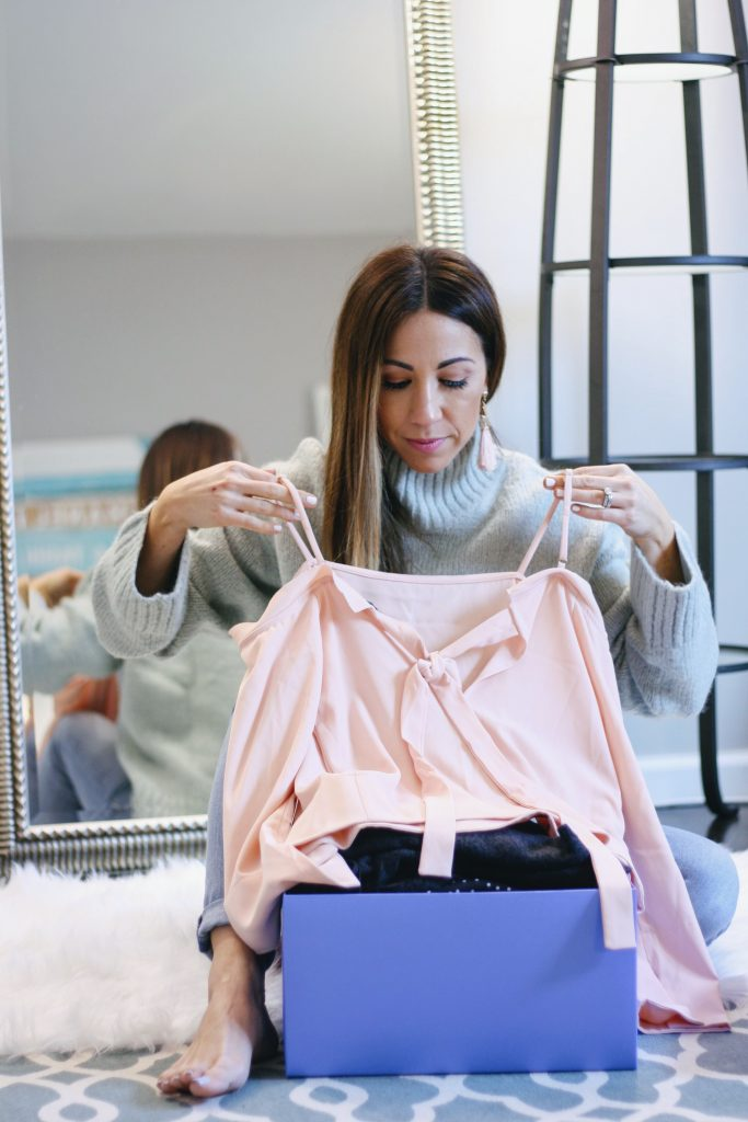 DAILYLOOK BOX REVIEW: SPRING FASHION featured by top New Jersey fashion blog, House of Leo: image of a woman sitting in front of a mirror holding her new pink off the shoulder top, including in her new Dailylook box
