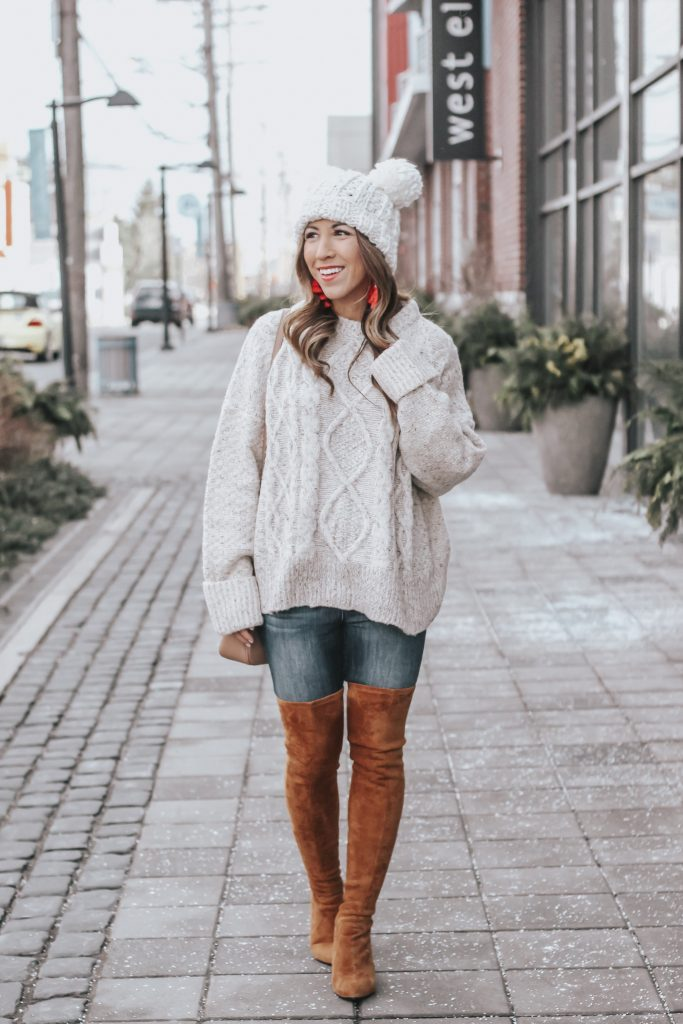 Cute winter outfit styled by top US fashion blog, House of Leo Blog: image of a woman wearing a Goodnight Macaroon knit sweater, Goodnight Macaroon over the knee suede leather boots, red tassel earrings and  a Red Dress white beanie hat