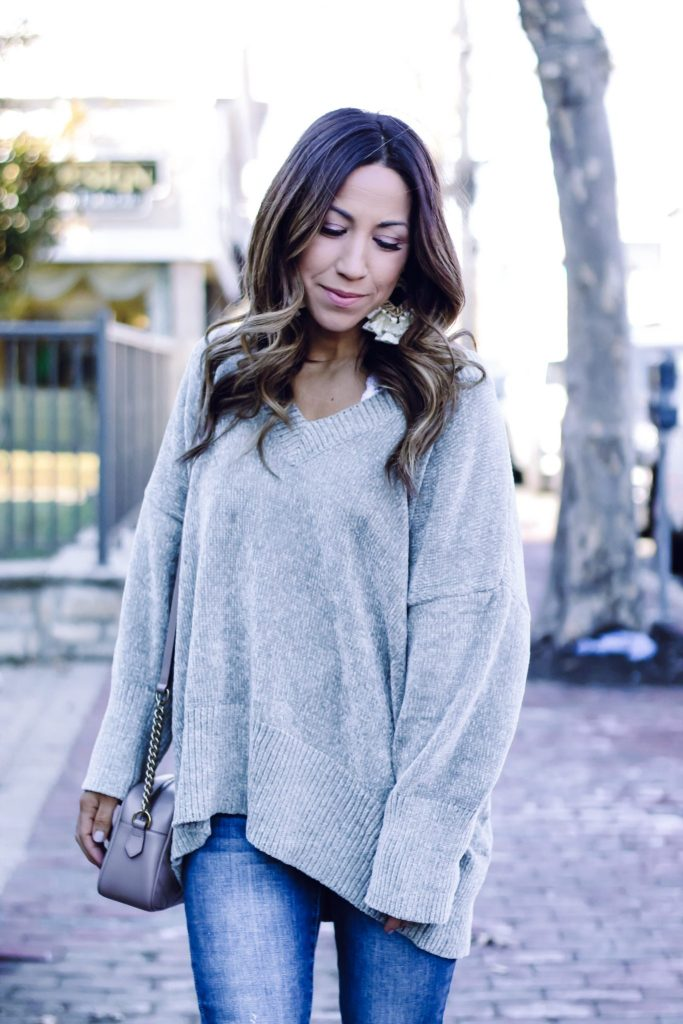 AFFORDABLE SWEATERS TO WEAR NOW FROM RED DRESS BOUTIQUE by top US fashion blog, House of Leo Blog: image of a woman wearing a chenille v-neck sweater and distressed jeans from Red Dress Boutique