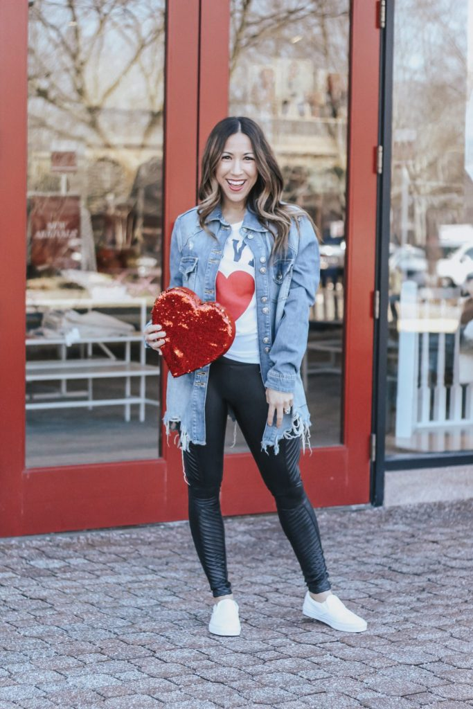 Casual Valentine's Day Outfit featured by top US fashion blog House of Leo Blog; Image of a woman wearing a denim jacket, heart shirt and faux leather leggings, all from Evereve.