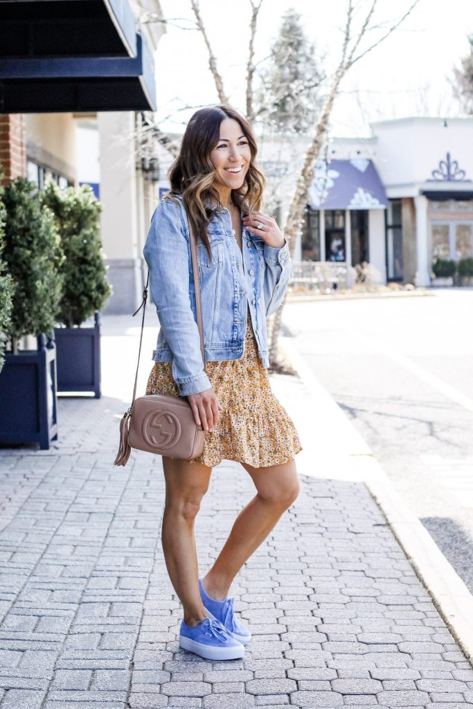Cute Floral Dresses from Goodnight Macaroon by top US fashion blog, House of Leo Blog: image of woman wearing a short yellow floral dress, Old Navy denim jacket and VANS blue platform sneakers