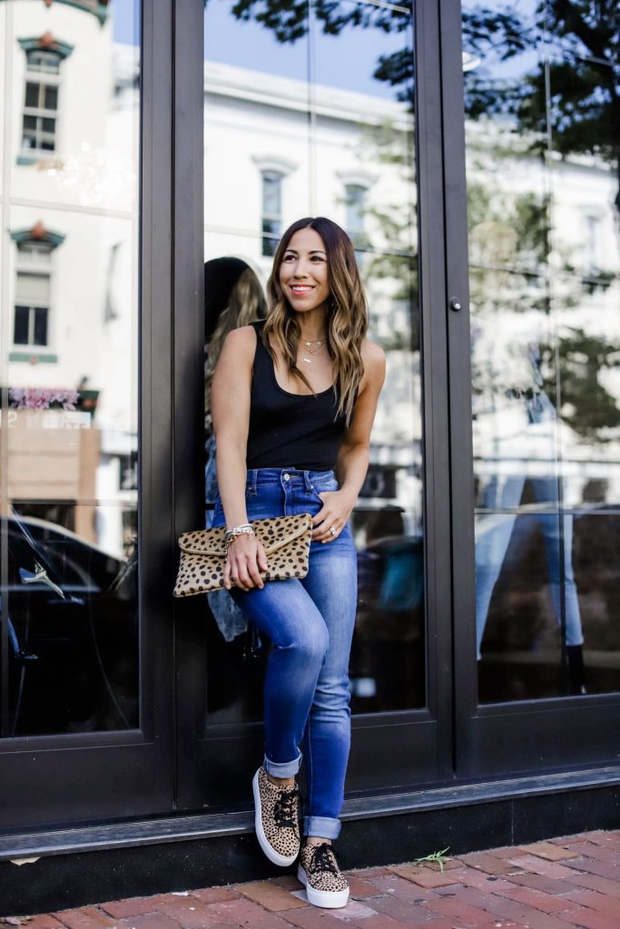 5 Simple Summer Looks from Red Dress Boutique by top US fashion blog, House of Leo Blog: image of woman wearing a black bodysuit, high waisted jeans, leopard platform sneakers and leopard clutch