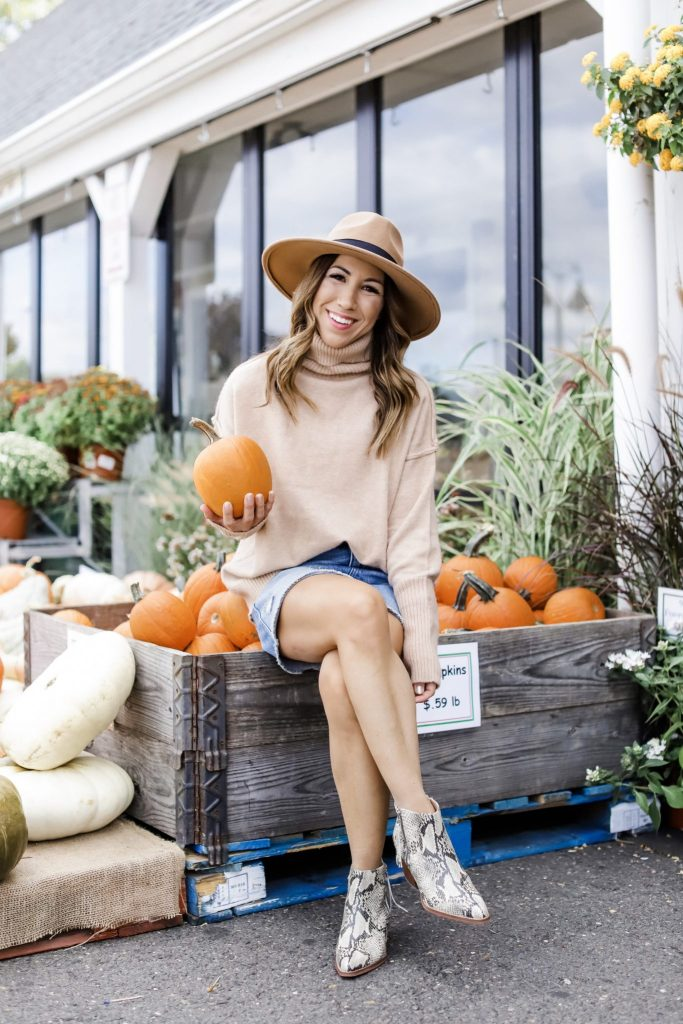 3 Ways To Wear A Denim Skirt This Fall by top US fashion blog, House of Leo Blog: image of woman wearing tan turtleneck, denim skirt and tan wool fedora hat and snakeskin booties