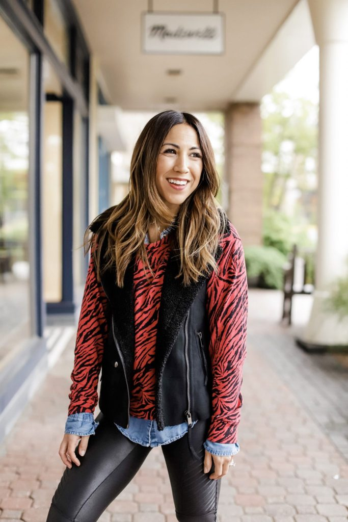 2 Edgy Outfits From Evereve by top US fashion blog, House of Leo Blog: image of woman wearing red zebra sweatshirt, black vest and denim shirt