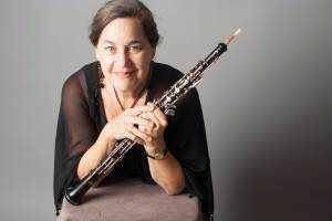 Woman poses with oboe.