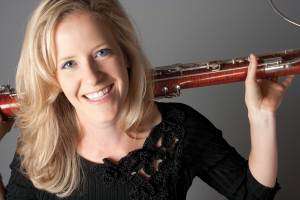 Woman poses with bassoon.