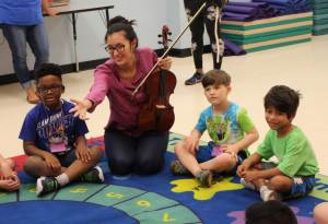 Woman with viola leads a musical activity for children at a summer camp.