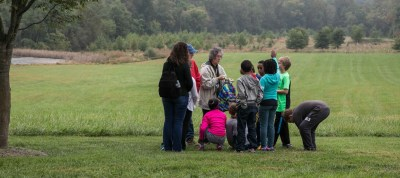 Students visiting historic Belmont hike with a volunteer naturalist during a field trip to the Howard County Conservancy