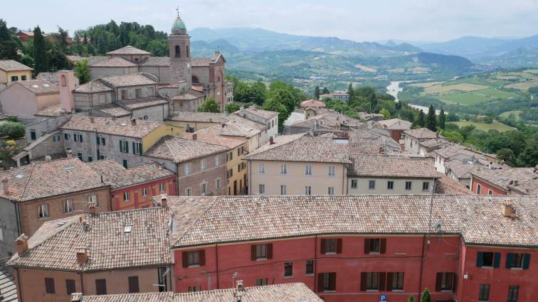Rooftops of buildings in Verucchio with rolling hills in the background