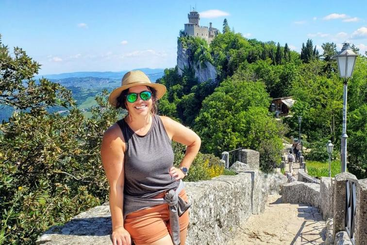 Smiling girl in a hat in front of the witches trail in San Marino