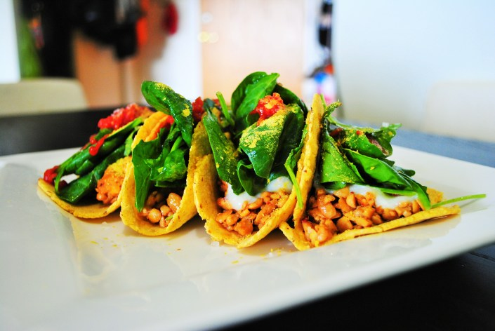 Tacos with spicy tempeh, white miso sauce and baby greens