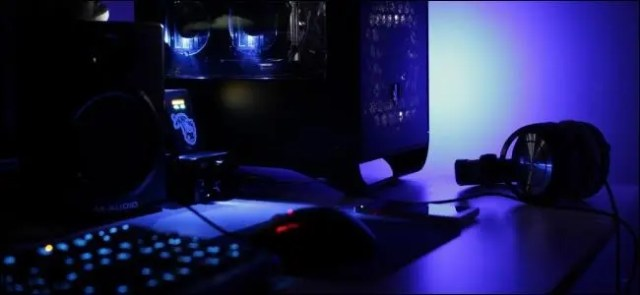 Desktop computer and headphones on a desk in a low-lit room.