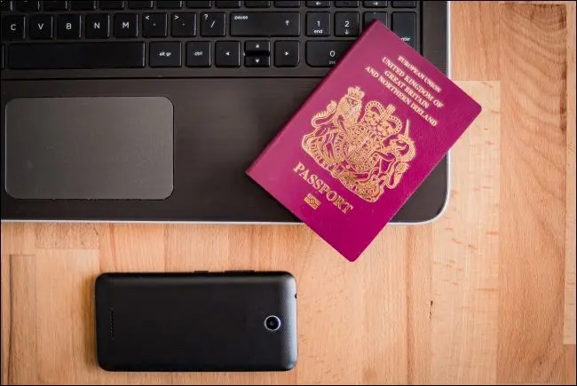 UK passport with laptop and smartphone
