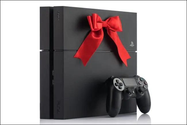 A PlayStation 4 console with a bow on it.