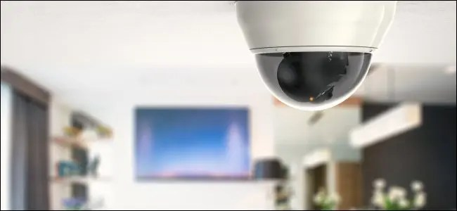 A security camera on a ceiling in front of a TV in a home.