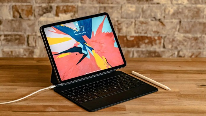 iPad with keyboard cover and stylus sitting on wood table