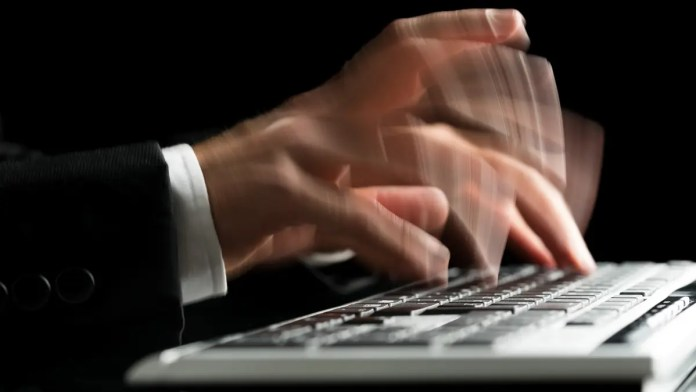 Close up of hands typing fast on a computer keyboard
