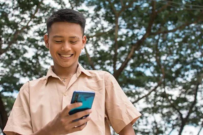 Someone laughing while looking at a phone.