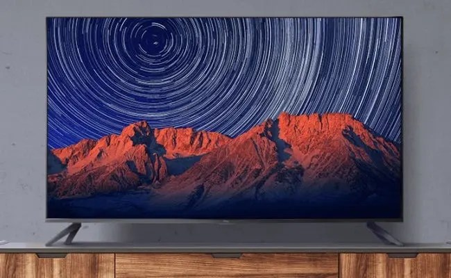 TCL TV on wooden entertainment center