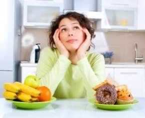 Beautiful Young Woman choosing between Fruits and Sweets to lose weight fast