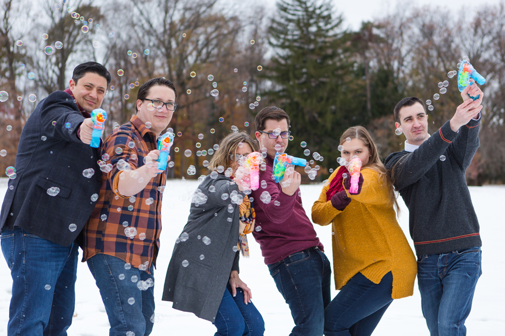 family poses with bubble guns