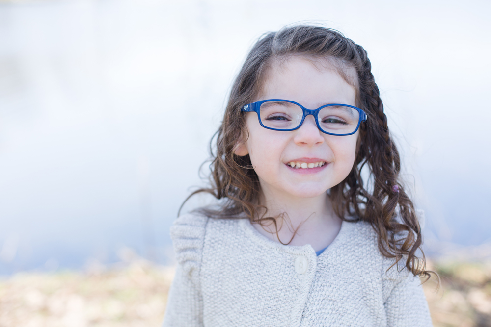 girl in blue glasses poses by lake